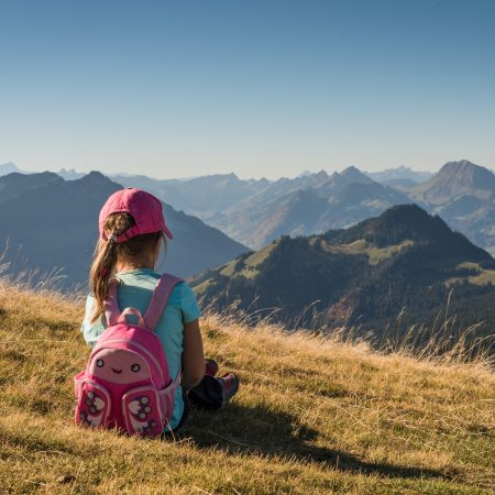 Girl sitting on hillside looking at mountains while wearing a backpack