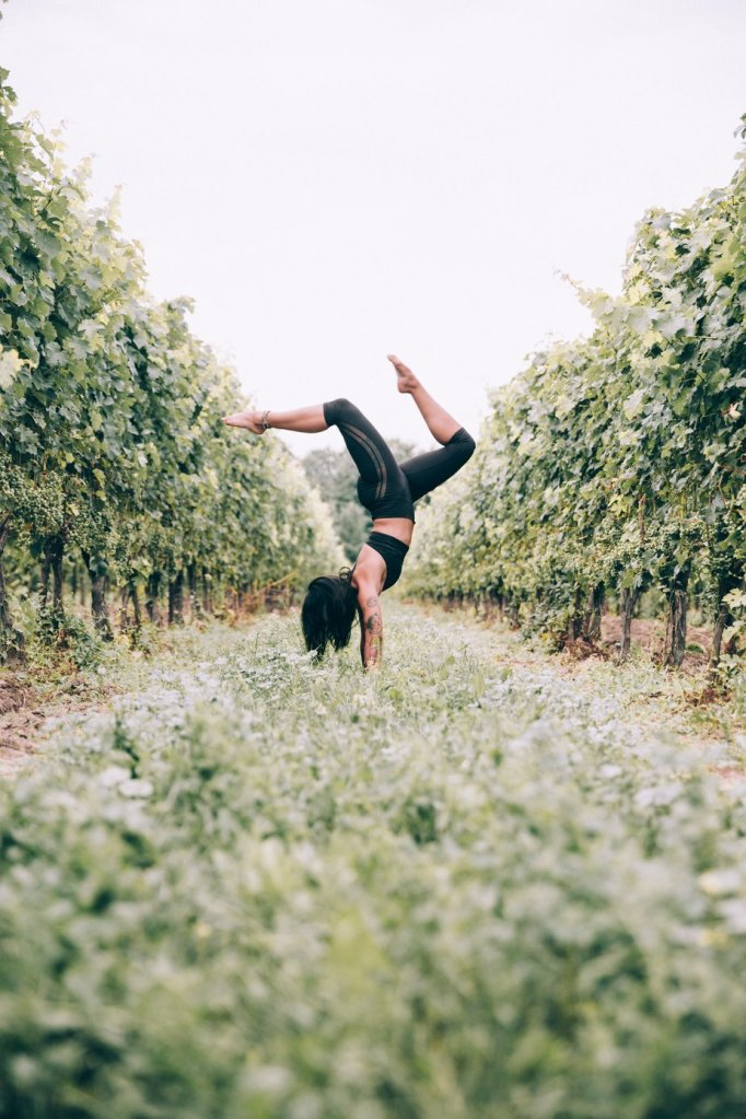 yoga practicing woman doing a handstand in an orchard